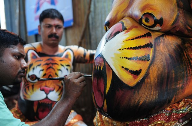 """Indian artists paint performers with body-paint depicting tigers as they prepare to take part in the """"Pulikali"""", or Tiger Dance, in Thrissur on September 17, 2016. (Photo by Arun Sankar/AFP Photo)"""
