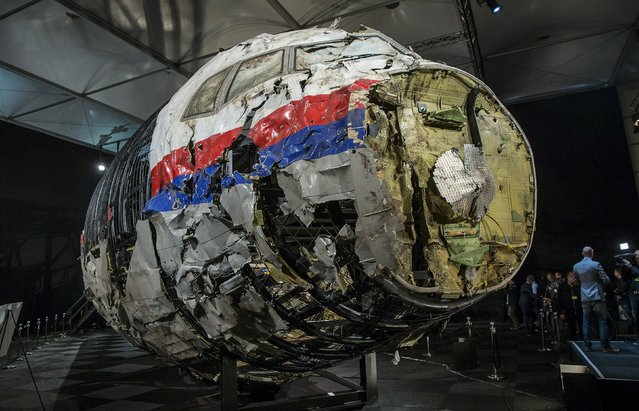 The reconstructed wreckage of the MH17 airplane is seen after the presentation of the final report into the crash of July 2014 of Malaysia Airlines flight MH17 over Ukraine, in Gilze Rijen, the Netherlands, October 13, 2015. Malaysian Airlines Flight 17 was shot down over eastern Ukraine by a Russian-made Buk missile, the Dutch Safety Board said on Tuesday in its final report on the July 2014 crash that killed all 298 aboard. (Photo by Michael Kooren/Reuters)