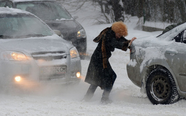 A woman pushes a jammed car as heavy snow falls in Lviv, Ukraine on March 15, 2013. (Photo by Yuriy Dyachyshyn/AFP Photo)