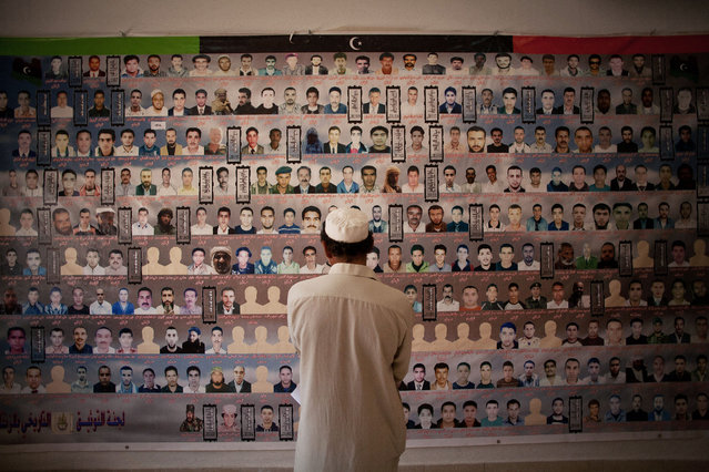 A Libyan man looks at a banner with photos of men who were killed during the revolution in Zintan, western Libya. Libyan rebels from the western town of Zintan emerged as heroes after playing a key role in last year's civil war that ousted Moammar Gadhafi, Monday, July 9, 2012. (Photo by Manu Brabo/AP Photo)