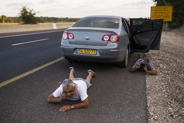 Israelis take cover on the side of a road as a siren sounds warning of incoming rockets outside the northern Gaza Strip, in this July 15, 2014 file photo. (Photo by Amir Cohen/Reuters)