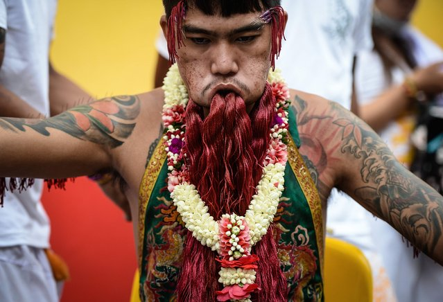 A devotee of the Nine Emperor Gods sits with coloured yarn through large piercings in his face during the annual Phuket Vegetarian Festival in the southern province of Phuket on October 1, 2016. (Photo by Lillian Suwanrumpha/AFP Photo)