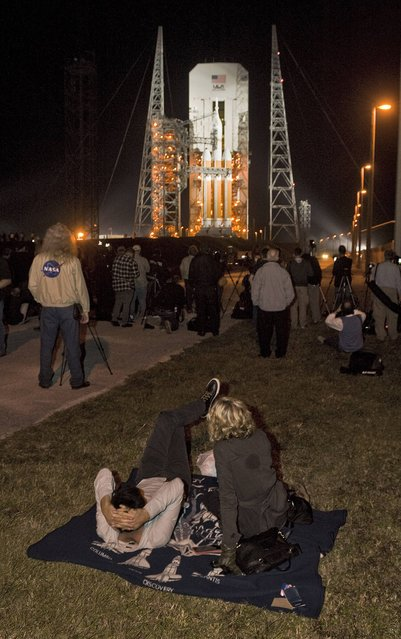 Social media bloggers watch for the the Mobile Service Tower to roll back from the Delta IV Heavy with the Orion spacecraft on launch pad 37B at Cape Canaveral Air Force Station in Cape Canaveral, Florida, December 4, 2014. The Orion ship is designed to carry crews beyond Earth to destinations such as asteroids, the Moon and Mars. NASA wants to test it first on an unmanned mission before allowing astronauts to climb aboard. (Photo by Steve Nesius/Reuters)
