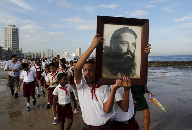"A student carries a picture of the rebel hero Camilo Cienfuegos during a gathering in honour of Cienfuegos at Havana's seafront wall ""El Malecon"", October 28, 2015. Cienfuegos was a commander of Fidel Castro's rebel army but died less than a year after their victory when his plane disappeared over the ocean on October 28, 1959 enroute from Havana to Camaguey. (Photo by Reuters/Stringer)"