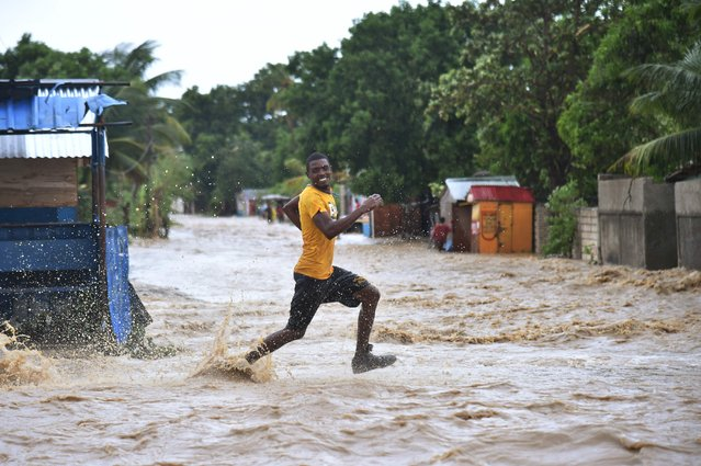 A man runs to cross the overflowing of the river Rouyonne, in the commune of Leogane Port-au-Prince, on October 5, 2016. Haiti and the eastern tip of Cuba – blasted by Matthew on October 4, 2016 – began the messy and probably grim task of assessing the storm's toll. Matthew hit them as a Category Four hurricane but has since been downgraded to three, on a scale of five, by the US National Hurricane Center. (Photo by Hector Retamal/AFP Photo)