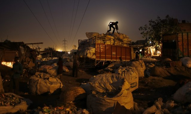 In this November 6, 2014 photo, a worker loads segregated trash for recycling on a truck on the outskirts of New Delhi, India. Rag picking is effectively the primary recycling system in India. While the rag pickers offer invaluable services to the city, they have few rights and are exposed to deadly poisons everyday. (Photo by Altaf Qadri/AP Photo)