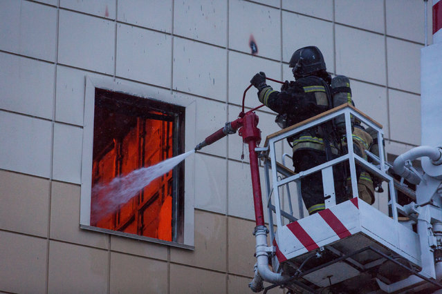 Members of the Emergency Situations Ministry work to extinguish a fire in a shopping mall in the Siberian city of Kemerovo, Russia March 25, 2018. (Photo by Maksim Lisov/Reuters)