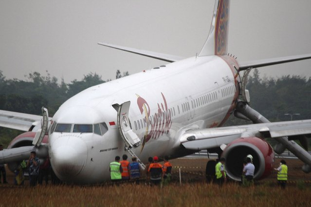 Airport officers stand next to a Batik Air Boeing 737-900ER aircraft that skidded off at the Adi Sucipto Airport in Yogyakarta, Indonesia November 6, 2015 in this picture taken by Antara Foto. There were no casualties in the accident. (Photo by Andreas Fitri Atmoko/Reuters/Antara Foto)
