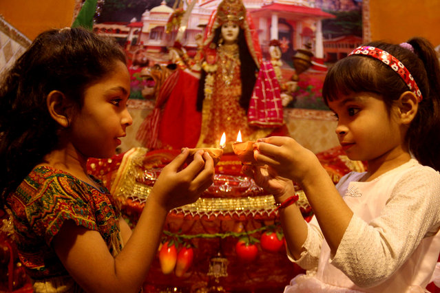 "Pakistani Hindu girls lights earthen lamps to celebrate Diwali festival in Hyderabad , Pakistan, 13 November 2020. The Diwali festival, also known as the ""Festival of Lights"", symbolizes the victory of Good over Evil. (Photo by Nadeem Khawer/EPA/EFE/Rex Features/Shutterstock)"