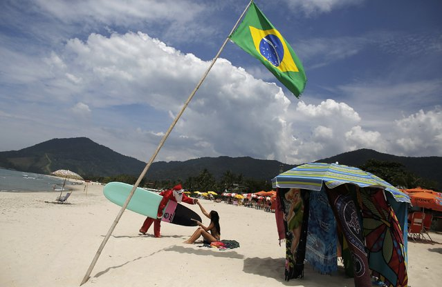 Carlos Bahia, dressed as Santa Claus, greets a woman next to a Brazilian flag at the Maresias beach, in the state of Sao Paulo December 9, 2014. (Photo by Nacho Doce/Reuters)