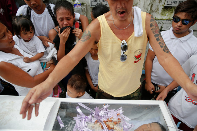 Friends and relatives of Gilbert Purgatorio, who was killed by masked gunmen, mourn around the coffin during his and his relative's funeral at a cemetery in Manila, Philippines October 11, 2016. (Photo by Damir Sagolj/Reuters)