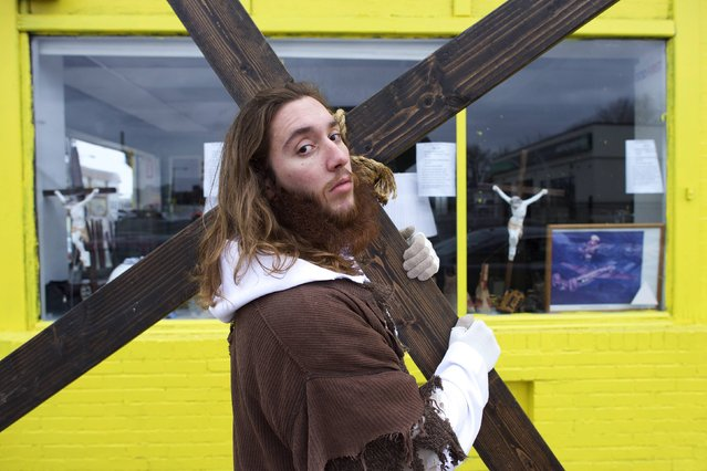 "Michael Grant, 28, ""Philly Jesus"", poses for a portrait in front of a store window featuring crucifixes with the 12 foot cross he carried 8 miles through North Philadelphia to LOVE Park in Center City as part of a Christmas walk to spread the true message of the holiday in Philadelphia, Pennsylvania December 20, 2014. (Photo by Mark Makela/Reuters)"