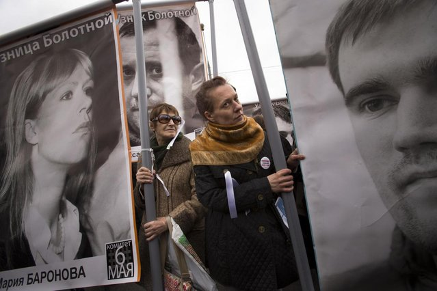 Opposition demonstrators hold posters of imprisoned protesters during a major protest rally in Bolotnaya Square in Moscow, Russia, Monday May 6, 2013. The rally marks the one-year anniversary of a protest on the eve of Putin's inauguration that ended in clashes between police and demonstrators. (AP Photo/Alexander Zemlianichenko)