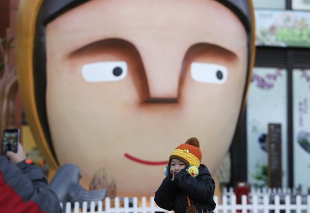 A boy poses for a photo with Christmas decorations in front of a shopping mall in Beijing, December 24, 2014. (Photo by Jason Lee/Reuters)