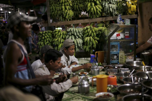 Workers eat dinner in a stall in the Thiri Mingalar market in Yangon November 6, 2015. (Photo by Jorge Silva/Reuters)
