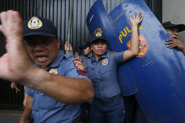 Riot police react as protesters force their way closer to the gates of the U.S. Embassy during a violent dispersal in Manila, Philippines Wednesday, October 19, 2016. The protesters, consisting of students, workers and tribespeople, were demanding an end to the presence of visiting U.S. troops in the Philippines and to support a call by President Rodrigo Duterte for a foreign policy not dependent on the U.S., the country's longtime treaty ally. (Photo by Bullit Marquez/AP Photo)