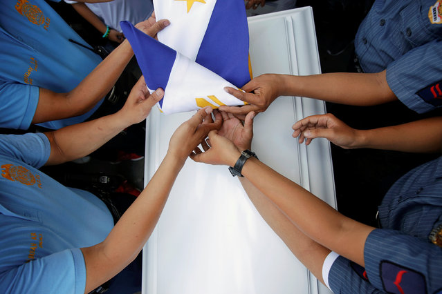 The national flag is folded over the coffin of Rancel Cruz, a police officer killed by an unknown gunman earlier this month, during his funeral in Manila, Philippines October 22, 2016. (Photo by Damir Sagolj/Reuters)
