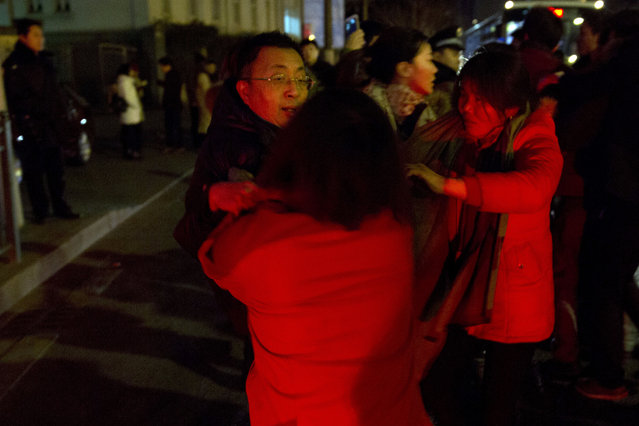 Relatives of victims of a deadly stampede, angered by the lack of information, drag a municipal officer, at left onto the road demanding answers in Shanghai, China, Thursday, January 1, 2015. (Photo by Ng Han Guan/AP Photo)