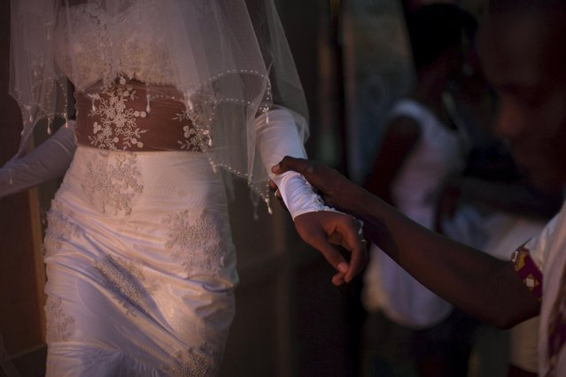 Model Coumba Soumare (L) wears a gown by Malian designer Tawati as she prepares to go onto the catwalk during the Festi'Bazin runway show in Bamako, Mali, October 16, 2015. (Photo by Joe Penney/Reuters)