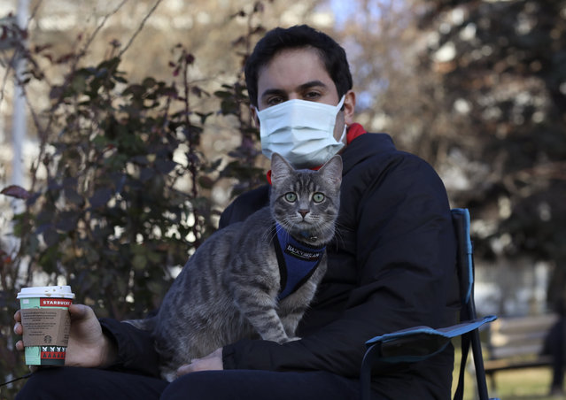 A man holds his cat as they enjoy good weather in a public garden. in Ankara, Turkey, Tuesday, December 29, 2020. Turkey has declared a four-day lockdown, starting on New Year's eve, to curb the spread of the coronavirus and President Recep Tayyip Erdogan has warned that parties and other large gatherings will not be tolerated. (Photo by Burhan Ozbilici/AP Photo)