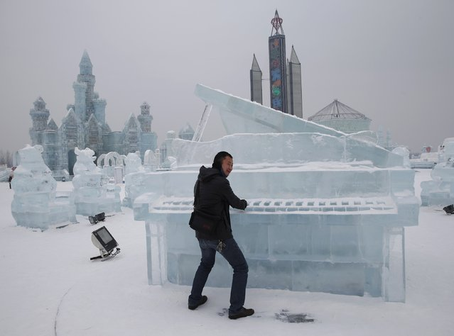 A visitor has his picture taken with a piano-shaped ice sculpture ahead of the 31st Harbin International Ice and Snow Festival in the northern city of Harbin, Heilongjiang province, January 4, 2015. (Photo by Kim Kyung-Hoon/Reuters)