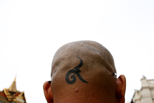 """A mourner's tattoo is seen on the back of his head as he walks in line into the Throne Hall at the Grand Palace for the first time to pay respects to the body of Thailand's late King Bhumibol Adulyadej that is kept in a golden urn in Bangkok, Thailand, October 29, 2016. The tattoo read: """"Number Nine"""". (Photo by Athit Perawongmetha/Reuters)"""