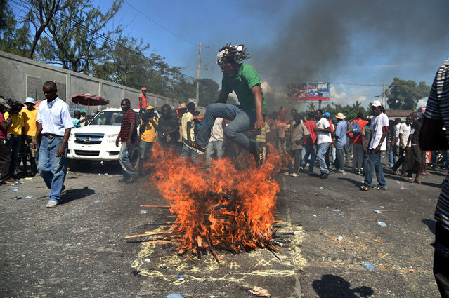 Supporters from the Fanmi Lavalas political party perform a voodoo ceremony before a march, in Port-au-Prince, on November 24, 2015. Supporters of Fanmi Lavalas and Petit Dessalines political parties marched to protest against the results given by the Provisional Electoral Council(CEP), against the Haitian President Michel Martelly, and against the candidate of the ruling party Jovenel Moise. (Photo by Hector Retamal/AFP Photo)