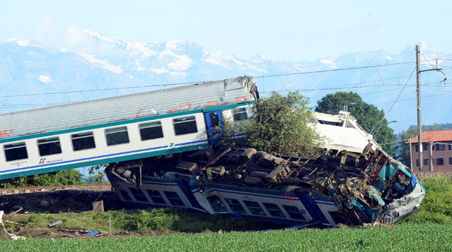 The twisted wreckage of a train that plowed into a truck last night is seen in Caluso, near Turin, Italy, May 24, 2018. (Photo by Massimo Pinca/Reuters)