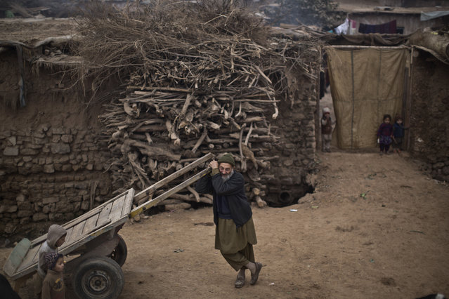 An elderly internally displaced Pakistani man from tribal areas stands in front of his mud home, waiting other men to head to work on the outskirts of Islamabad, Pakistan, Wednesday, January 7, 2015. (Photo by Muhammed Muheisen/AP Photo)