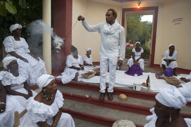 Voodoo Priest Herold Josue, also the National Director of Ethnology Bureau, swings incense as he leads a voodoo ceremony marking the fifth anniversary of the earthquake at the National Ethnology Bureau in Port-au-Prince, Haiti, Monday, January 12, 2015. (Photo by Dieu Nalio Chery/AP Photo)
