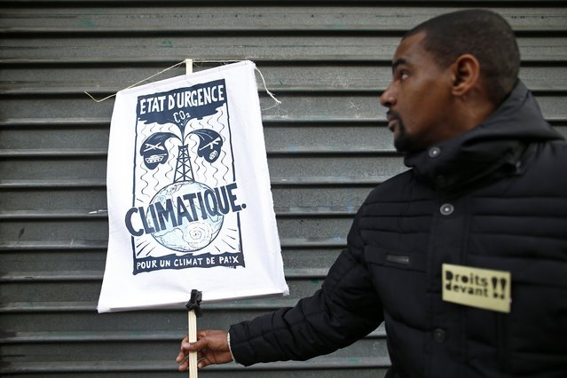 """People form a human chain to show solidarity for climate change after the cancellation of a planned climate march following shootings in the French capital, ahead of the World Climate Change Conference 2015 (COP21), in Paris, France, November 29, 2015. The slogan reads """"Climatic emergency state, for a climate of peace"""". (Photo by Benoit Tessier/Reuters)"""
