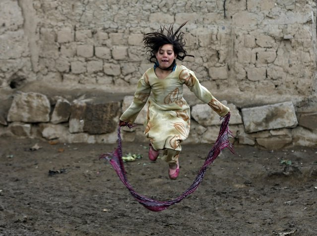 An internally displaced Afghan girl plays near their shelter at a refugee camp in Kabul January 13, 2015. (Photo by Omar Sobhani/Reuters)