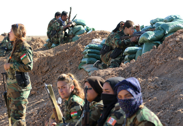 Iranian-Kurdish female fighters sit near a sand berm during a battle with Islamic State militants in Bashiqa, near Mosul, Iraq on November 3, 2016. (Photo by Ahmed Jadallah/Reuters)