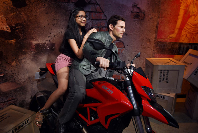 An Indian visitor sits on a bike with the wax statue of American actor Tom Cruise at the Madame Tussauds Delhi in New Delhi, India on June 6, 2018. (Photo by Money Sharma/AFP Photo)