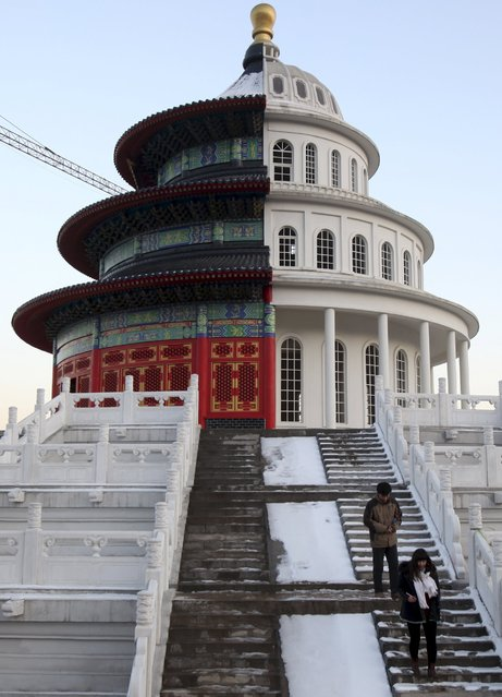 People walk down the stairs near a building, which is made by half of a replica of the Qinian Hall of the Temple of the Heaven (L) and half of a western building, at a studio for productions of films and television shows on the outskirts of Shijiazhuang, Hebei province, China, December 3, 2015. (Photo by Reuters/Stringer)