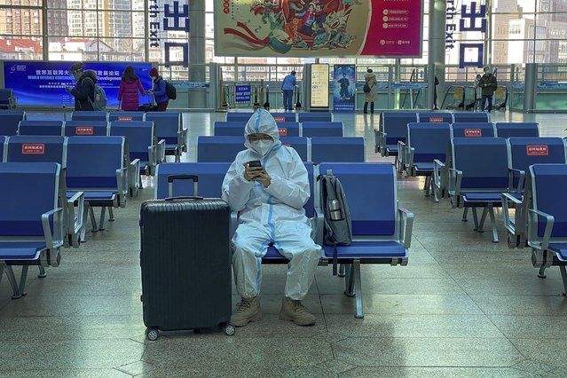 A traveller wearing protective gear to help curb the spread of the coronavirus sits alone on the bench as he waits for his train at the South Train Station in Beijing, Thursday, January 28, 2021. (Photo by Andy Wong/AP Photo)