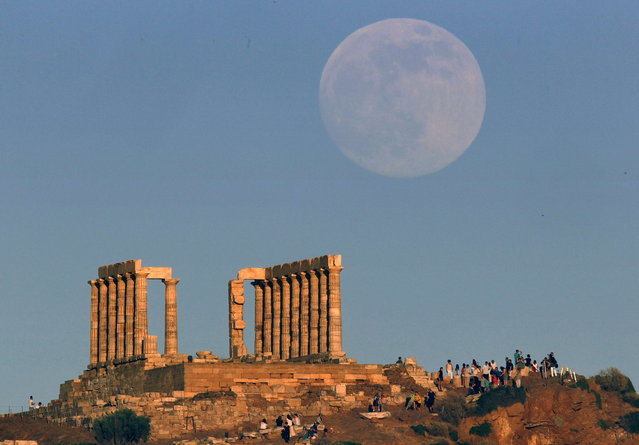 The moon rises over the temple of Poseidon, the ancient Greek god of the seas, as tourists enjoy the sunset in Cape Sounion some 60 km east of Athens June 22, 2013. The moon will reach its full stage on Sunday, and is expected to be 13.5 percent closer to earth during a phenomenon known as supermoon. (Photo by Yannis Behrakis/Reuters)