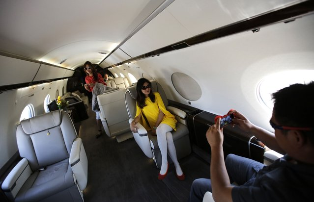 A visitor takes a photograph of another in a Gulfstream G650 aircraft at the Asian Business Aviation Conference and Exhibition (ABACE) at Hongqiao International Airport in Shanghai in this April 15, 2014 file photo. (Photo by Carlos Barria/Reuters)