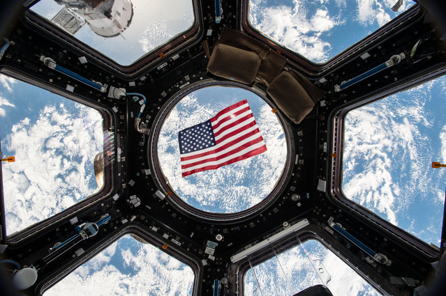An American flag is visible in the windows of the cupola aboard the International Space Station. Thanks to a bill passed by Texas legislators in 1997 that put in place technical voting procedure for astronauts – nearly all of whom live in Texas – they have the ability to vote from space through specially designed absentee ballots. To preserve the integrity of the secret vote, the ballot is encrypted and only accessible by the astronaut and the county clerk responsible for casting the ballot. (Photo by NASA)