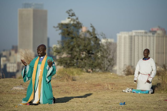Worshippers pray in the Hillbrow neighbourhood overlooking down town Johannesburg, on July 1, 2013. (Photo by AFP Photo)