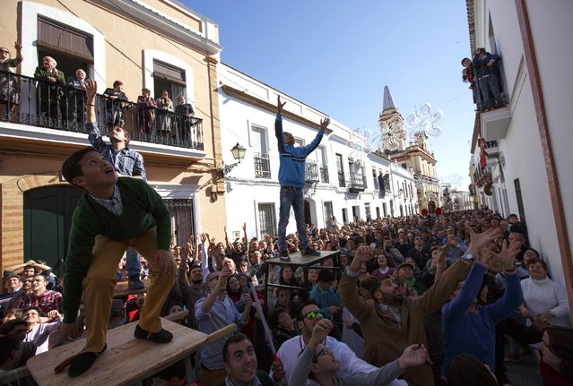 People wait to catch food thrown from balconies during the annual San Antonio Abad (Saint Anton Abbott) festival in Trigueros, southwest Spain January 25, 2015. (Photo by Marcelo del Pozo/Reuters)