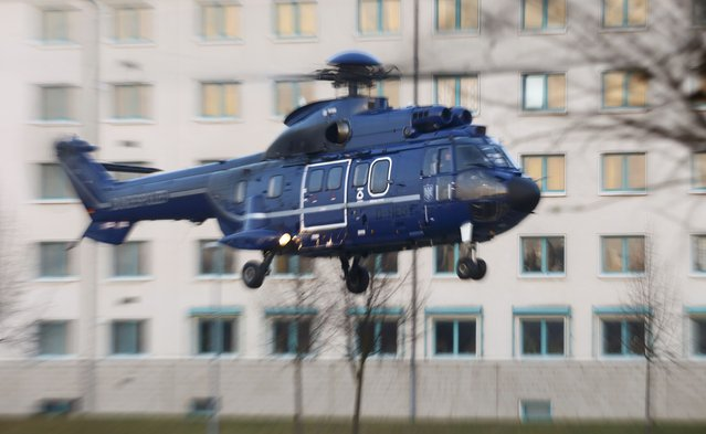 Members of German federal police Bundespolizei use a helicopter as they demonstrate their skills during a presentation of the new unit for arrests and securing evidence (BFE) in Ahrensfelde near Berlin, Germany December 16, 2015. (Photo by Hannibal Hanschke/Reuters)