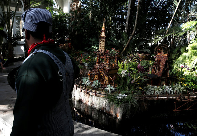 A worker in a conductors outfit stands by as model trains travel past a scaled model of the former Luna Park at Coney Island built entirely with plant parts during a media preview of the 25th annual Holiday Train Show at the New York Botanical Garden in the Bronx borough of New York City, U.S., November 14, 2016. (Photo by Mike Segar/Reuters)