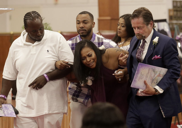 Nailah Winkfield, the mother of Jahi McMath, center, cries as she leaves funeral services for McMath with husband Martin Winkfield, left, McMath's uncle Omari Sealey, second from left, and attorney Christopher Dolan, right, at Acts Full Gospel Church in Oakland, Calif., Friday, July 6, 2018. Dozens of family members, friends and other mourners filed into a Northern California church Friday for the funeral of a teenage girl at the center of a medical and religious debate over brain death. (Photo by Jeff Chiu/AP Photo)