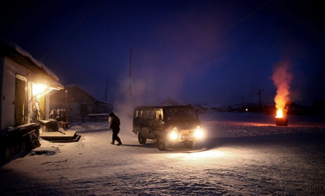 A man leaves his van and walks into Oymyakon, Russia's only shop as an oil drum full of paper waste burns in the distance in January 2013. (Photo by Amos Chapple/REX Features)