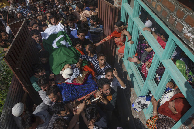 Kashmiri villagers carry the body of a teenage boy Tamsheel Ahmed Khan during his funeral procession in Vehil village, some 65 Kilometers south of Srinagar, Indian controlled Kashmir, Tuesday, July 10, 2018. Government forces fired at protesters Tuesday in Indian-controlled Kashmir, killing Khan and wounding at least 120 more who had been trying to reach the site of a gunbattle in which soldiers killed two rebels, police and residents said. (Photo by Dar Yasin/AP Photo)