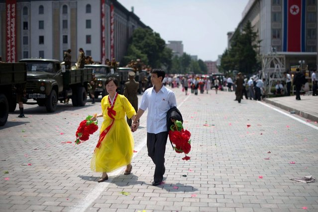 A North Korean couple hold hands as they walk on Kim Il-Sung square following a parade marking the 60th anniversary of the Korean war armistice in Pyongyang on July 27, 2013.  North Korea mounted its largest ever military parade on July 27 to mark the 60th anniversary of the armistice that ended fighting in the Korean War, displaying its long-range missiles at a ceremony presided over by leader Kim Jong-Un. (Photo by Ed Jones/AFP Photo)