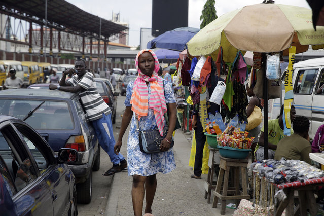 A woman walks past people selling on the street in Lagos Saturday, October 24, 2020. (Photo by Sunday Alamba/AP Photo)