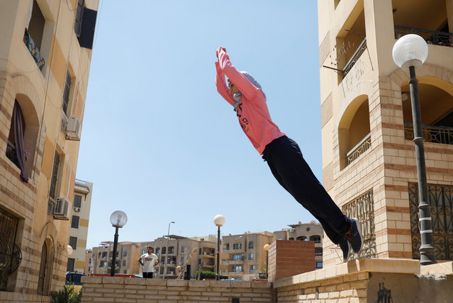 """An Egyptian woman from Parkour Egypt """"PKE"""" practices her parkour skills around buildings on the outskirts of Cairo, Egypt on July 20, 2018. """"It needs more time to evolve and the sport needs to spread more so that people would learn about it"""", said Zayneb Helal, one of the players. (Photo by Amr Abdallah Dalsh/Reuters)"""