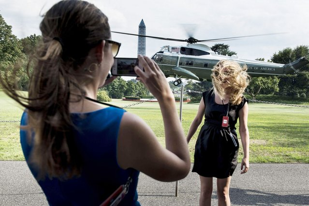 A woman has her photo taken as Marine One lands with US President Barack Obama on the South Lawn of the White House in Washington, on July 31, 2013. (Photo by Brendan Smialowski/AFP Photo)